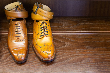 Brown and tan full grain leather shoes with belts on wooden display in men shoes boutique store.
