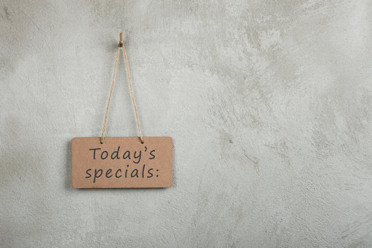 notice board, blackboard, chalkboard with text Today's specials on copy space grey cement wall
