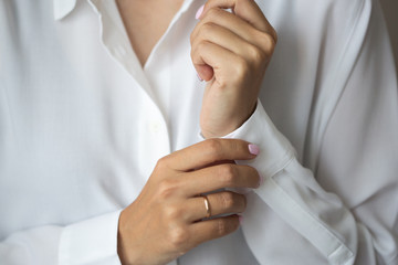 Close-up photo of elegant light pink manicure over white shirt background, tender women's hands with perfect nails, spa and care