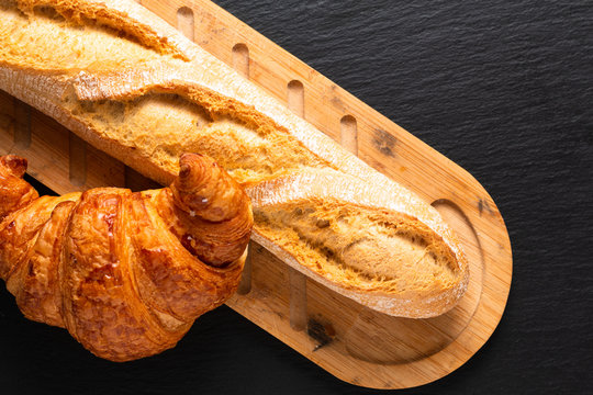 Food concept French croissant and baguette on black slate board with copy space