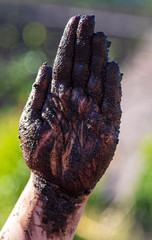 Hands of a boy in black mud on nature