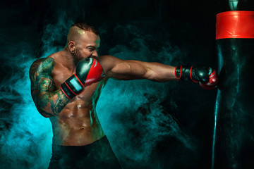Sportsman with tattoos, man boxer fighting in gloves with boxing punching bag. Isolated on black background with smoke. Copy Space.