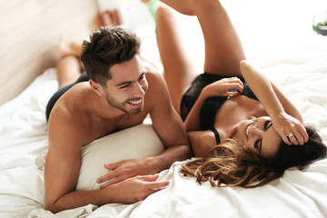 Young couple lying and laughing in the bed.