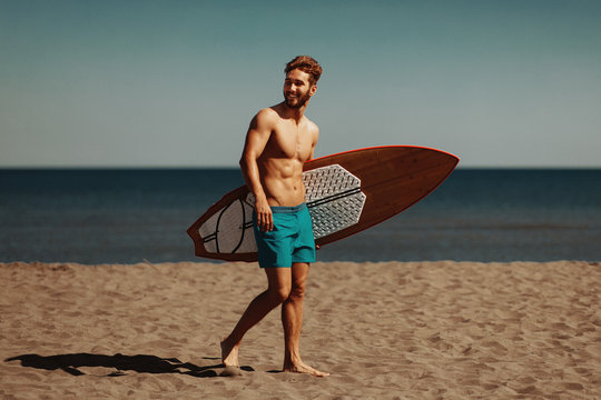 Young man and woman with a surf board on the beach