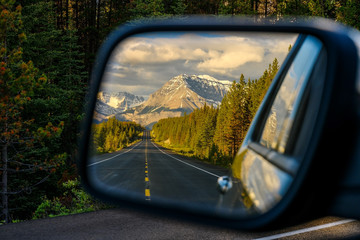 Driving through a mountain road and watching the beautiful scenery in the rearview mirror in the icefields parkway near Jasper Wall mural