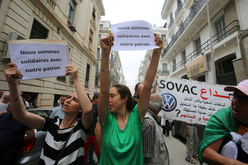 People carry banners in Algiers