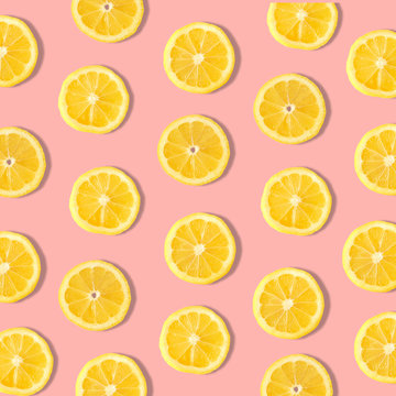 Summer fruit pattern of lemon slices on a pastel pink background