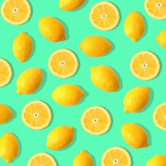 Summer fruit pattern of lemons and lemon slices on a teal green background