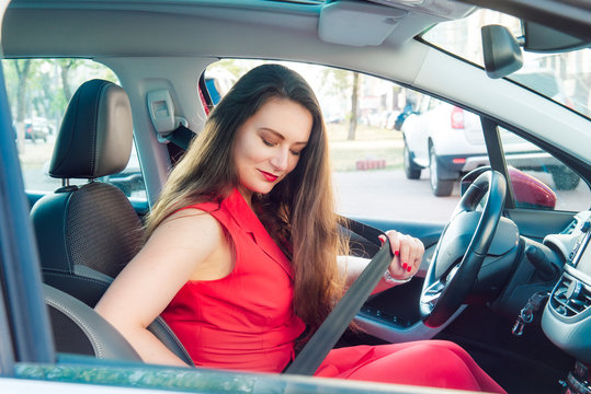 Portrait of business lady, caucasian young woman driver in red summer suit fastening car seat belt while sitting behind the wheel car. Safe driving concept. Selective focus, copy space.