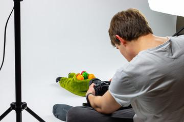 junger Hobby Fotograf macht Stockphotos vor weißer leinwand