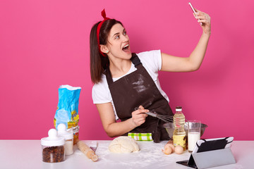Chef cook confectioner or baker in brown apron, white t-shirt, red hairband, making cake at table, doing selfie on mobile phone, posing with open mouth isolated over pink background in studio.