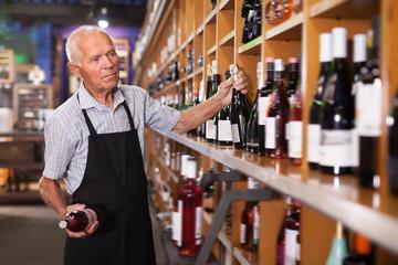 Elderly male vintner holding out bottle of wine