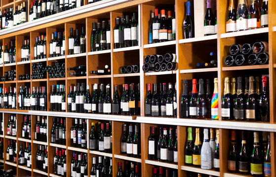 Rows of wine bottles on shelves in modern wine store waiting for customers