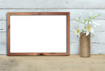 Horizontal A4 Old Wooden Frame mockup near a bouquet of lilies stands on a wooden table on a painted white wooden background. Rustic style, simple beauty. 3d render.