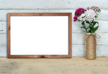 Foto auf Leinwand Weiß Vertical A4 Old Wooden Frame mockup near a bouquet of sweet-william stands on a wooden table on a painted white wooden background. Rustic style, simple beauty. 3d render.