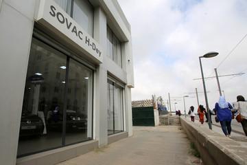 People walk past SOVAC showroom in Algiers