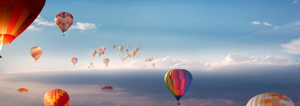 Viele Heißluftballons fliegen  über den Wolken
