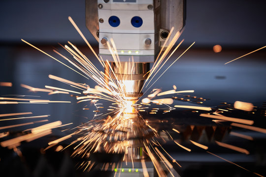 Laser cutting. Metal machining with sparks on CNC laser engraving maching