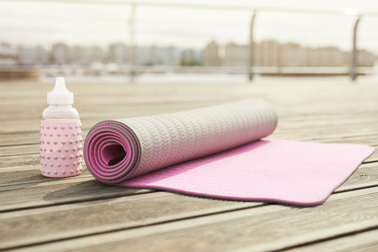 Background image of pink yoga mat set for workout on wooden pier outdoors, copy space