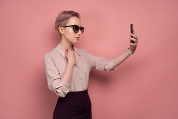 Pink-haired young woman with sunglasses takes a selfie on her smartphone, pink background