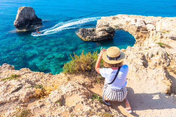 Cyprus. Tourists at Love bridge. The girl takes pictures of the bridge of love from above. The cliffs in the ocean water. The Cape Greco. Ayia Napa. The riding a water scooter in Mediterranean sea.