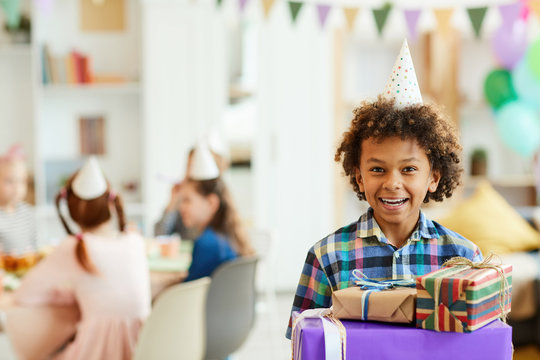 Portrait of happy African-American boy holding gift boxes posing during birthday party with friends, copy space