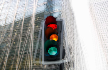 Traffic lights multiple exposure image. Traffic light showing red against of modern office block building. Business and modern life concept.