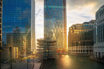 London, UK. Canary Wharf Banking and business area at  sunset. Lights reflection in the dock water.
