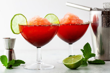 Red Frozen Margarita, refreshing cocktail on the table and lime with mint