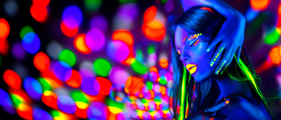 Sexy girl dancing in neon lights. Fashion model woman with fluorescent makeup posing in UV on bright background Wall mural