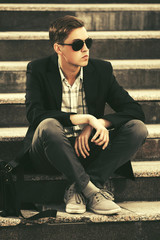 Young handsome business man in sunglasses sitting on steps