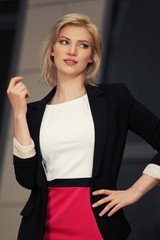 Young fashion business woman in black blazer on city street