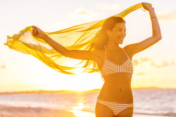 Happy Asian woman with healthy body wellness and wellbeing concept Bikini girl feeling free in wind with yellow scarf carefree in sunset beach vacation travel.