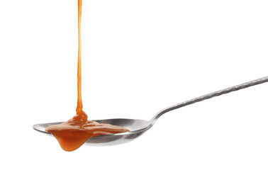 Tasty caramel sauce pouring into spoon isolated on white
