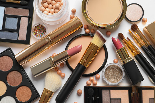 Different luxury makeup products on white background, top view