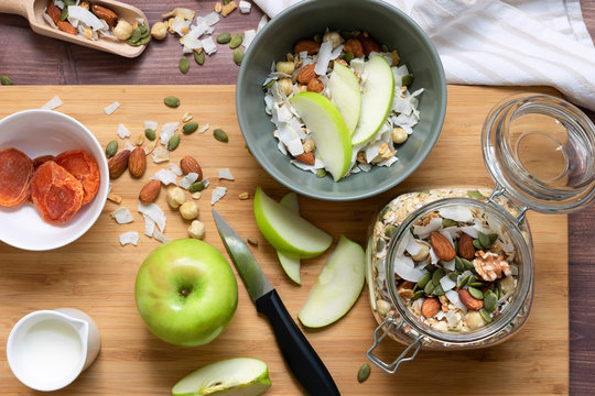 Preparation of a healthy breakfast bowl; granola, dried apricots and sliced apple.