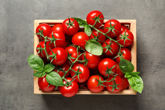 Crate with fresh cherry tomatoes on stone background, top view