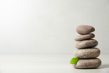 Photo sur Aluminium Detente Stack of spa stones with leaf on light background. Space for text