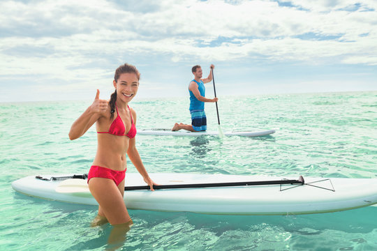 Paddleboard beach people on stand-up paddle boards surfing in ocean on Hawaii beach. Mixed race couple woman and Caucasian man enjoying watersport.