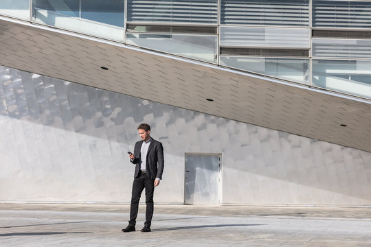 Businessman using mobile phone app texting outside of office in urban modern city building background. Young caucasian man holding smartphone for business work.