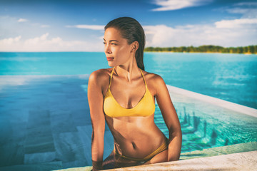 Wall Mural - Sexy Asian bikini model woman sun tanning in infinity pool at luxury hotel in Bora bora , Tahiti, French Polynesia. Swimsuit body summer vacation travel tan.