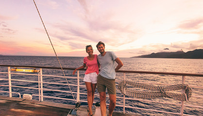 Wall Mural - Cruise travel couple on honeymoon vacation cruise ship destination luxury lifestyle. Happy interracial people tourists on boat at sunset sailing away.
