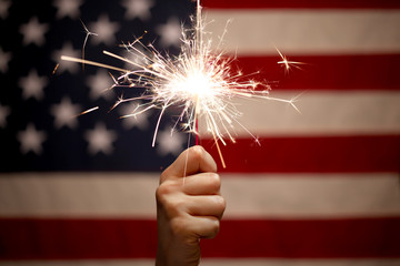 Wall Mural - Hand holding lit sparkler in front of the American Flag for 4th of July celebration
