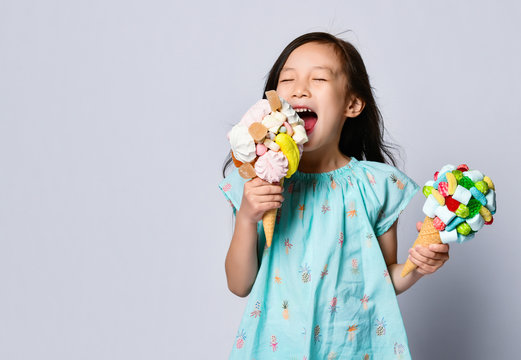 Baby girl kid eating two sweet big ice-cream in waffles cones with tasty raspberry marshmallow marmalade