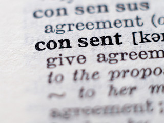 Dictionary definition of word consent. Selective focus.