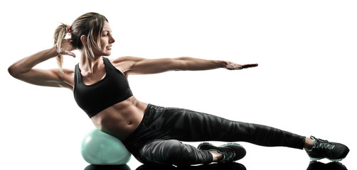 one caucasian woman exercising pilates fitness soft ball exercises isolated silhouette on white...
