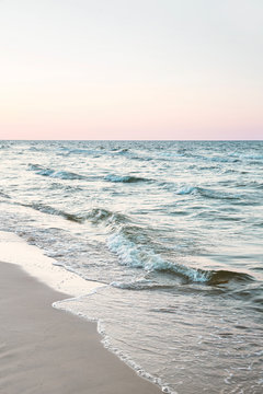 seascape: white sandy beach and waves on the shore at dawn, subtle pastel-colored sunset sky in the background