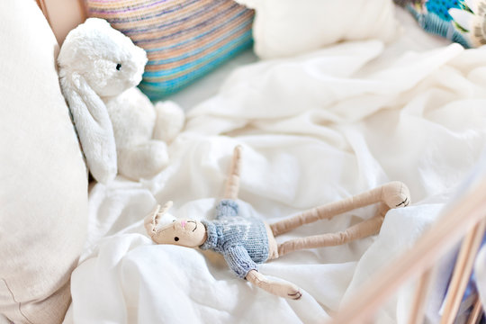 Hare toy dolls on the white sheet, bed with pillows