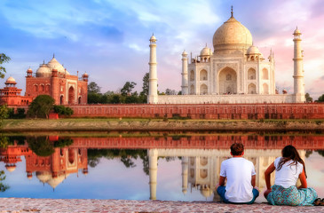 Wall Mural - Taj Mahal sunset view from Mehtab Bagh on the banks of river Yamuna with a tourist couple enjoying a romantic moment.
