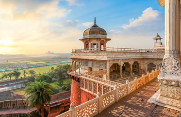 Agra Fort - Medieval Indian fort made of red sandstone and marble with view of dome at sunrise. View of Taj Mahal at a distance as seen from Agra Fort. Fotomurales